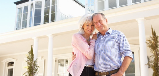 retired couple standing in front of home