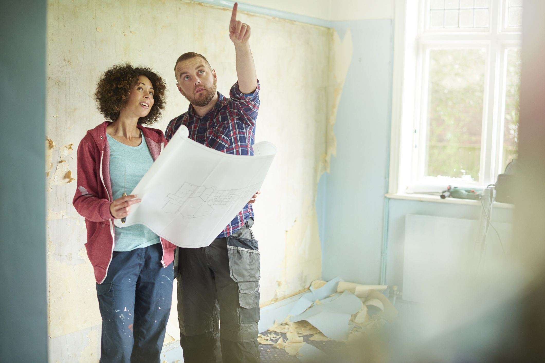 a young couple take time out from scraping walls in her new house to check against their architect plans