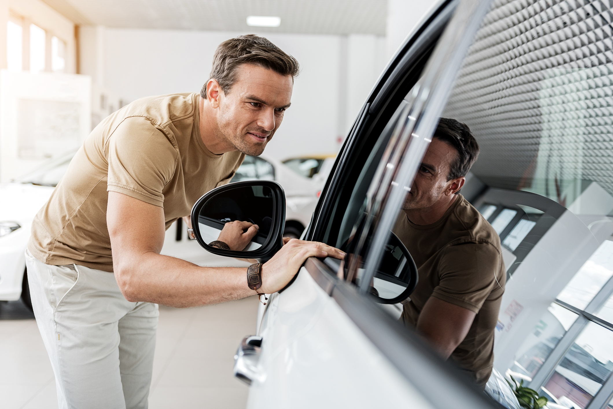 miling man expressing concernment while looking at passenger compartment through window of automobile
