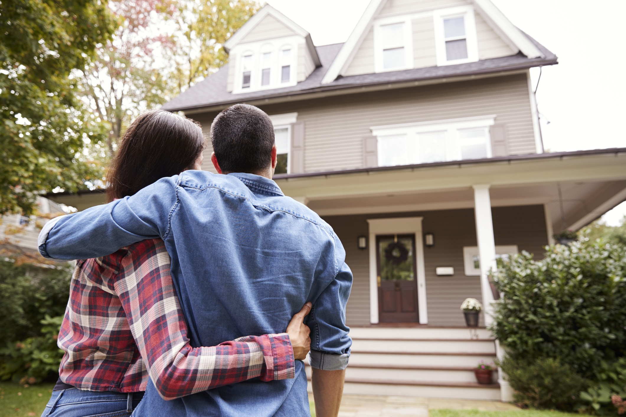Rear View Of Loving Couple Looking At House
